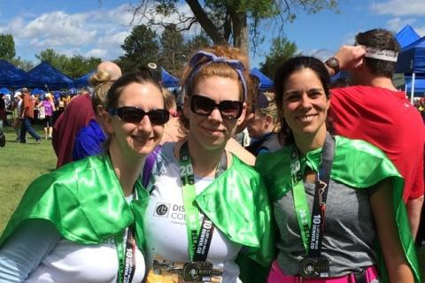 photo of 3 female runners with green Disability Law Colorado capes and colfax marathon relay medals around their necks
