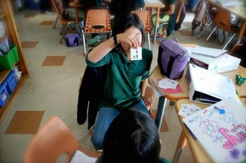 student in a classroom holding up a flashcard