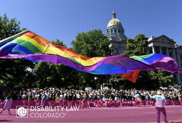 picture of Colorado pride parade with a big PRIDE flag and parade goers